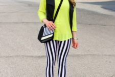 With neon green shirt, black vest, yellow shoes and printed bag
