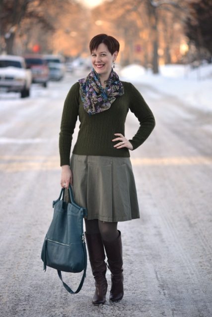 With olive green shirt, gray skirt, high boots and blue bag