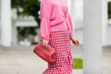 With pink sweater, red pumps and clutch