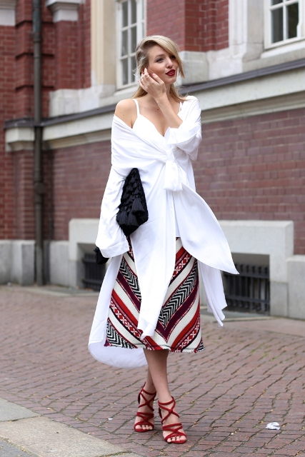 With unique white shirt, red sandals and black clutch