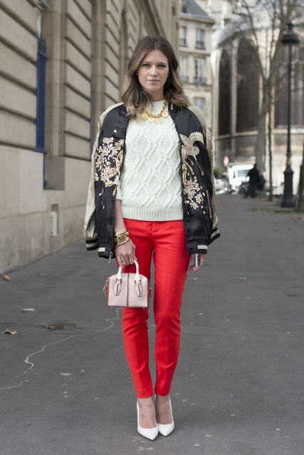 With white sweater, printed bomber jacket, red pants and mini bag