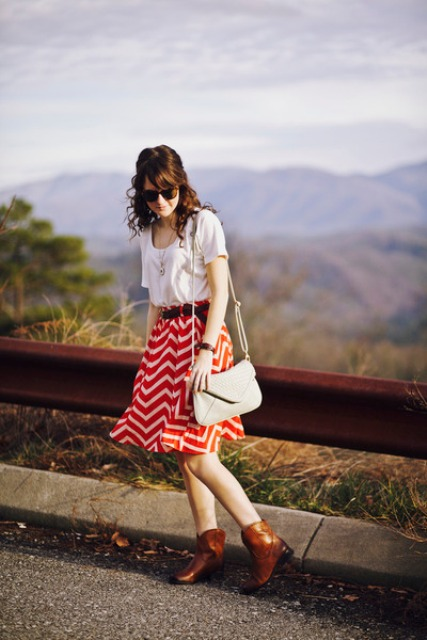 With white t shirt, beige bag and brown boots