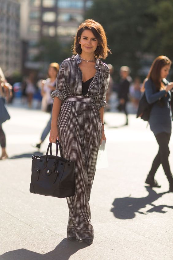 a black and white gingham jumpsuit with wide pants, long sleeves, a black top, a statement necklace and a comfy bag