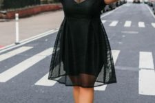 03 a black knee dress with a sheer overdress, an illusion neckline and trim, black heels