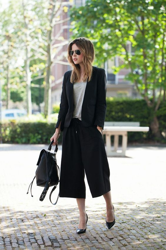 a black pantsuit with culottes, a neutral tee, black heels and a backpack for a masculine feel