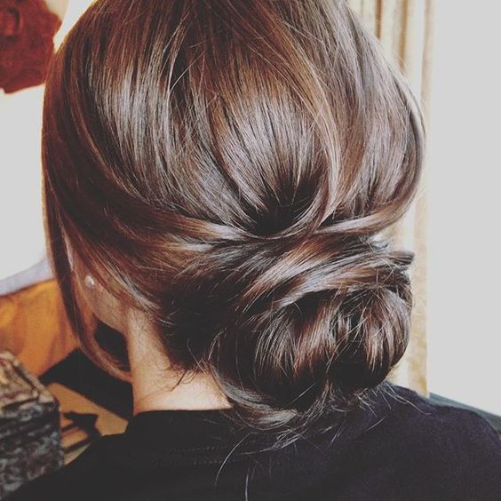a twisted low bun with some hair down is an elegant and chic idea for the office