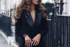 04 a chic black tuxedo outfit with long sleeves and a double breast, a chic clutch and watch