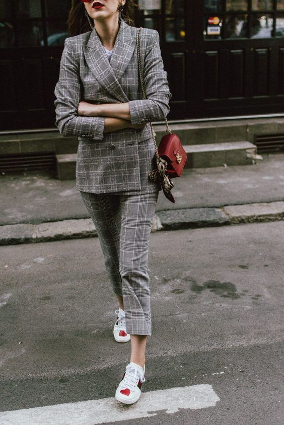 a plaid grey suit with cropped pants, a white tee, heart printed sneakers and a red bag