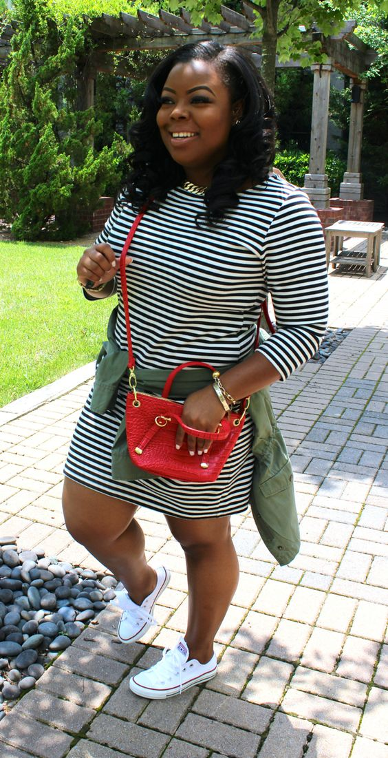 a striped long sleeve dress, white converse sneakers, a red bag and an olive green jacket