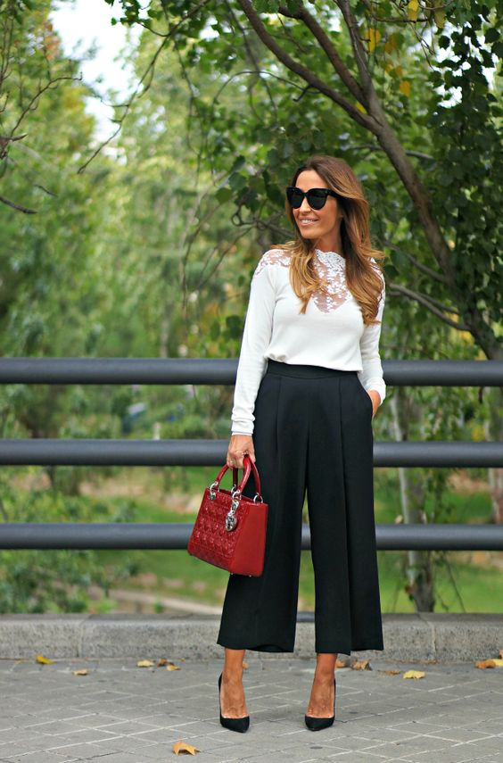 black culottes, black heels, a white sihrt with lace inserts and a red bag