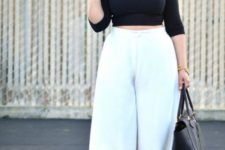 05 a black cropped top with long sleeves, white culottes, black shoes and a bag