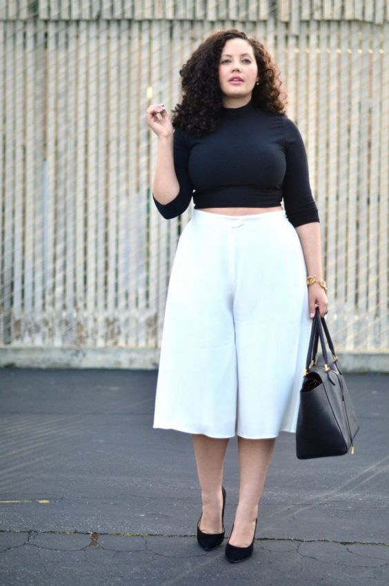 a black cropped top with long sleeves, white culottes, black shoes and a bag