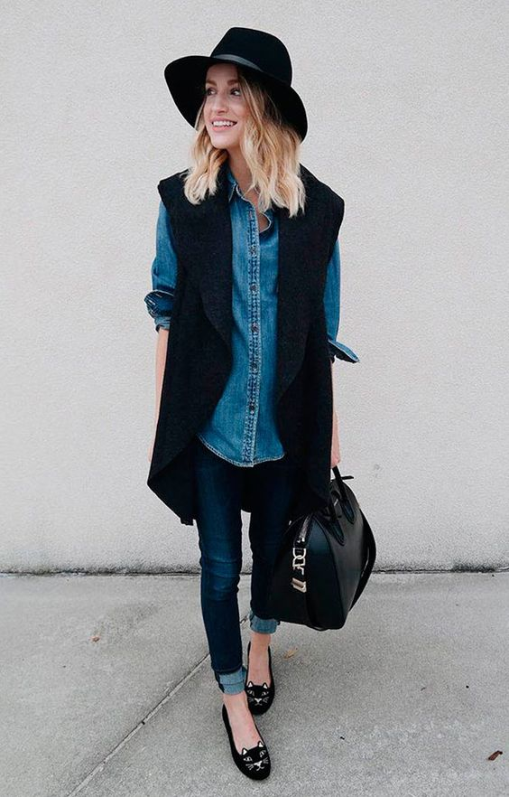navy cuffed skinnies, an oversized denim shirt, black kitty flats, a black long vest, a black hat and bag