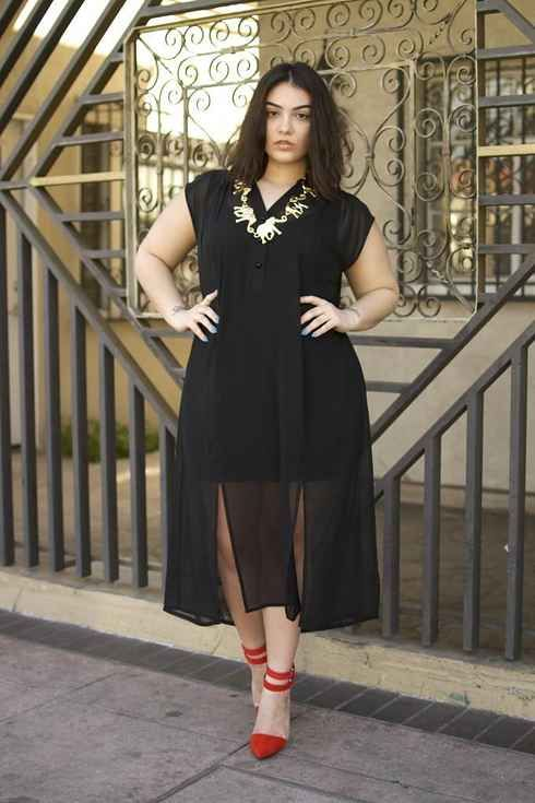 a black mini dress with a sheer midi overdress, a statement necklace and red shoes