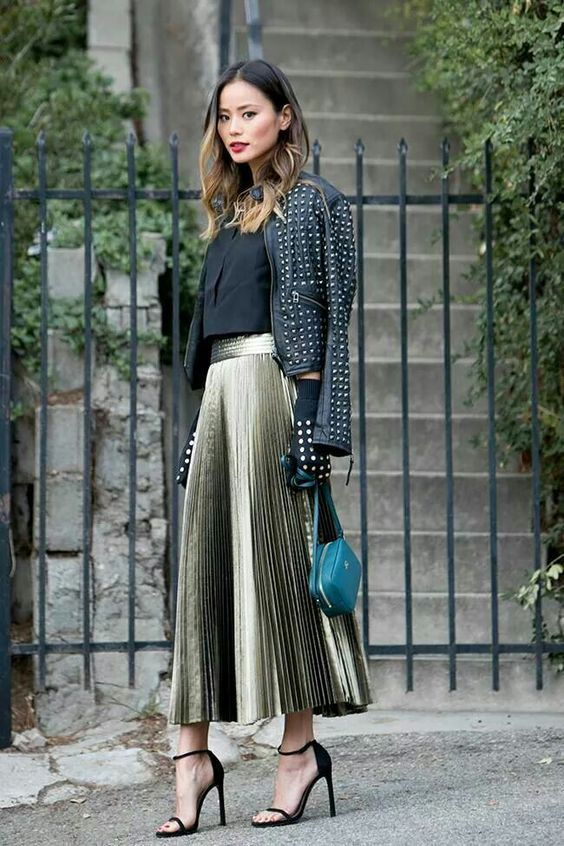 a metallic pleated midi skirt, a black top top, a leather jacket and a small dark green bag