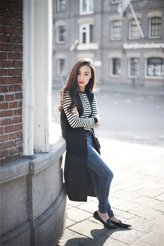 navy skinnies, a striped top, a black long vest and black flats for a casual and comfy look
