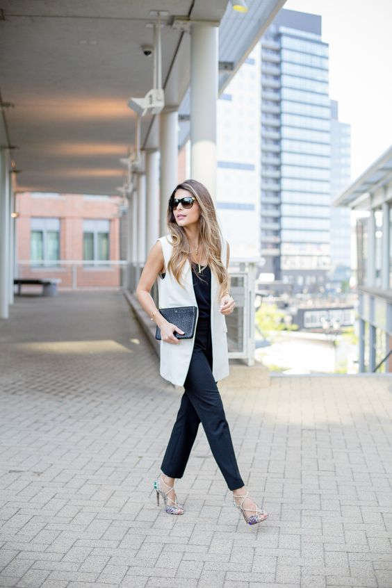 a black jumpsuit, a white long vest, metallic strappy heels and a black clutch for a professional look