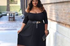 07 a black off the shoulder midi dress with a color block effect and a pleated skirt, a clutch and heels