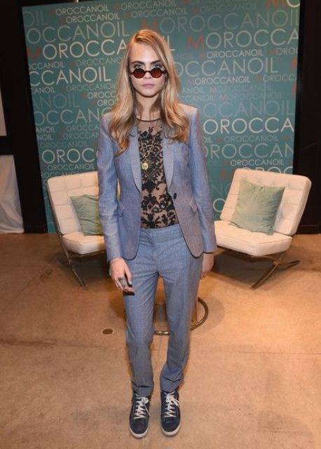 a grey pantsuit with a sheer black lace top and grey leather sneakers by Cara Delevigne