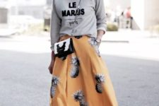 07 a grey printed sweatshirt, a bold yellow midi skirt with a pineapple print, white sneakers and a crossbody