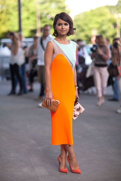 a modern catchy dress of white and orange with color blocking, orange shoes and a refined clutch