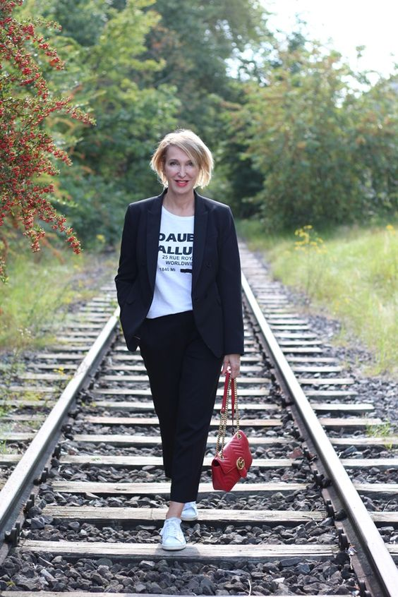 a black oversized pantsuit with cropped pants, a printed tee, white sneakers and a red bag