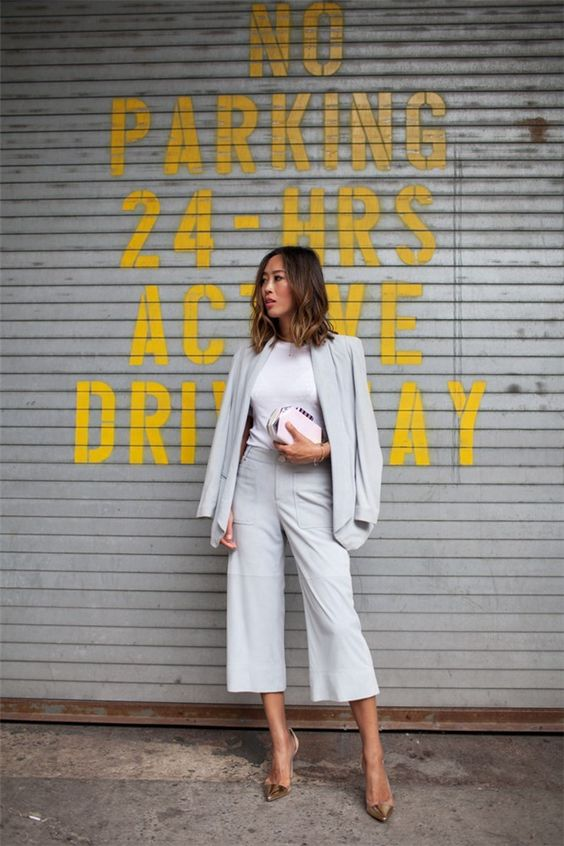 a light grey pantsuit with culottes, a white tee, metallic shoes and a clutch