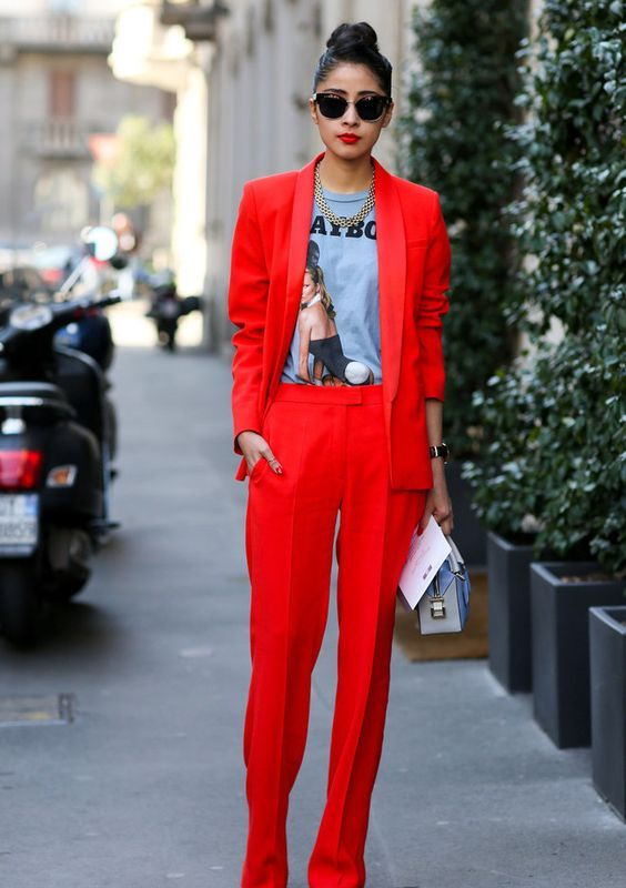 a red pantsuit with extra long pants, a printed tee, a statement necklace, a small bag for a street style look