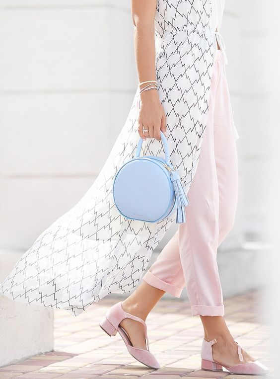 a tiny powder blue round bag with tassels adds a romantic feel to the look