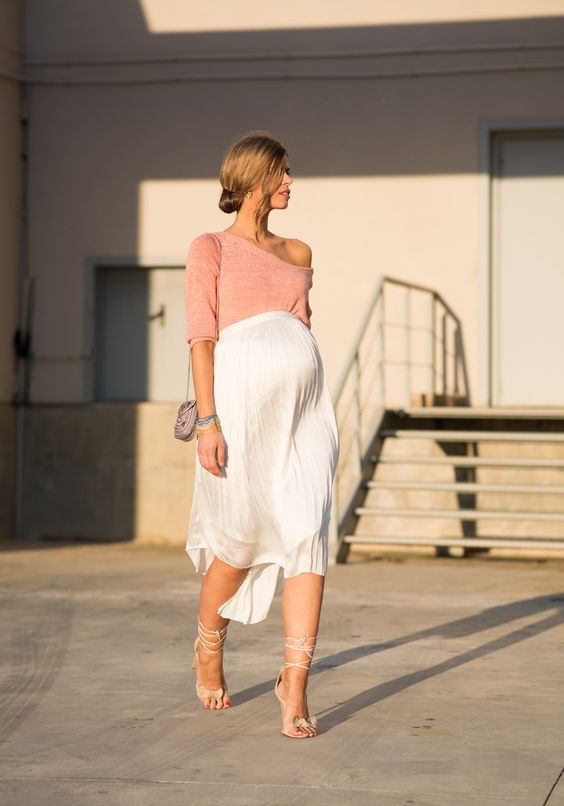 a blush one shoulder top with sleeves, a white pleated skirt, lace up shoes