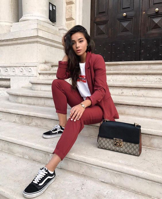 a burgundy pantsuit with a printed tee and black sneakers for a casual feel