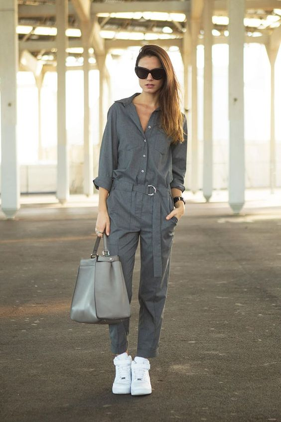 a casual grey jumpsuit with long sleeves, a ash with a buckle, a grey bag and white sneakers for a casual work look