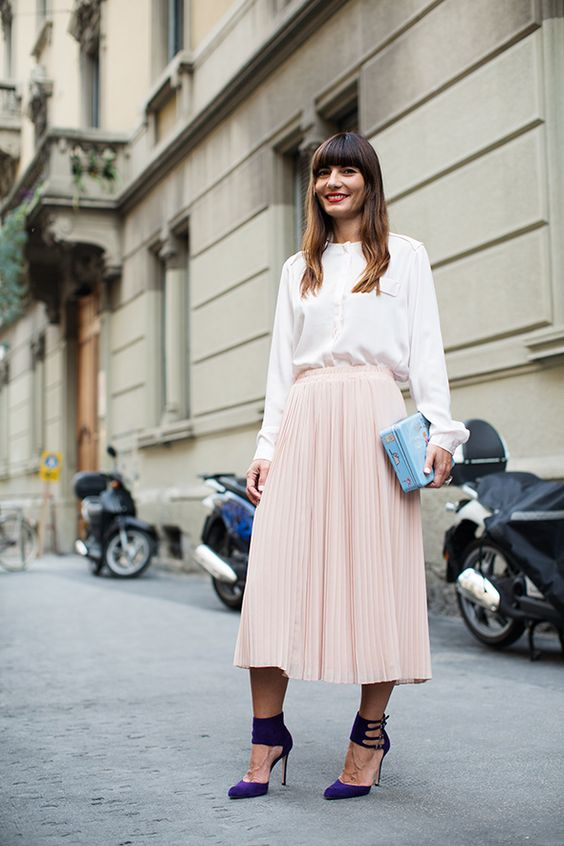 a white blouse, a blush pleated midi, a printed blue clutch and purple striped shoes