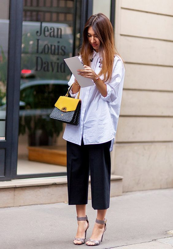 black culottes, a long white shirt, metallic heels and a color block bag for a creative job