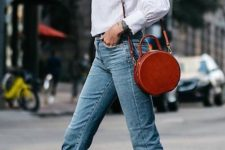 11 a cognac-colored leather round bag adds an eye-catchy touch to the casual outfit