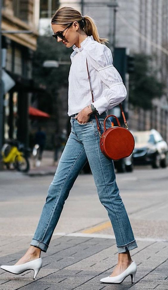 a cognac colored leather round bag adds an eye catchy touch to the casual outfit