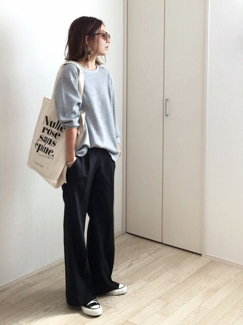 a grey sweatshirt, black wide pants, black sneakers
