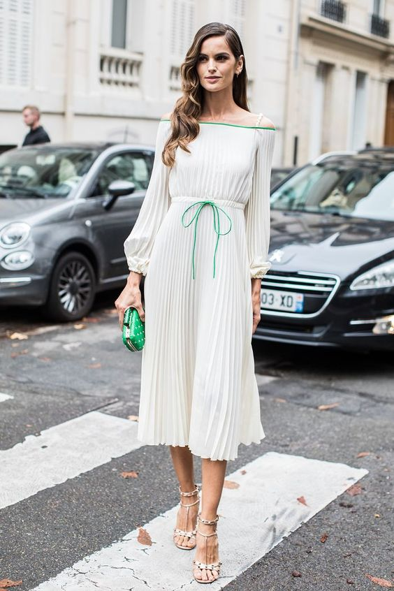 a romantic pleated off the shoulder midi dress with green touches and a matching clutch