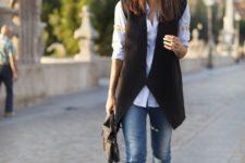 11 blue skinnies, a white shirt, a black geometric cut vest, color block shoes and a black bag