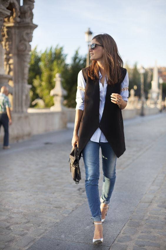 blue skinnies, a white shirt, a black geometric cut vest, color block shoes and a black bag