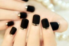 11 matte black nails with a gold strip for a bold and elegant look