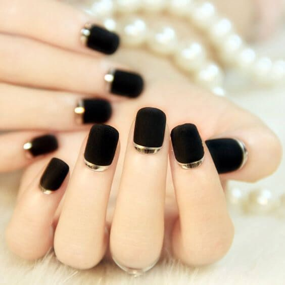 matte black nails with a gold strip for a bold and elegant look