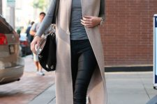 12 black boots, black pants, a grey turtleneck and a beige long vest for a bold casual look