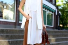12 brown culottes, a long white top with a slit, a long white vest, brown strappy shoes and a bag