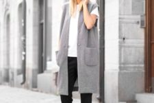 13 black cropped pants, a white tee, white sneakers and a grey oversized long vest for a trendy feel
