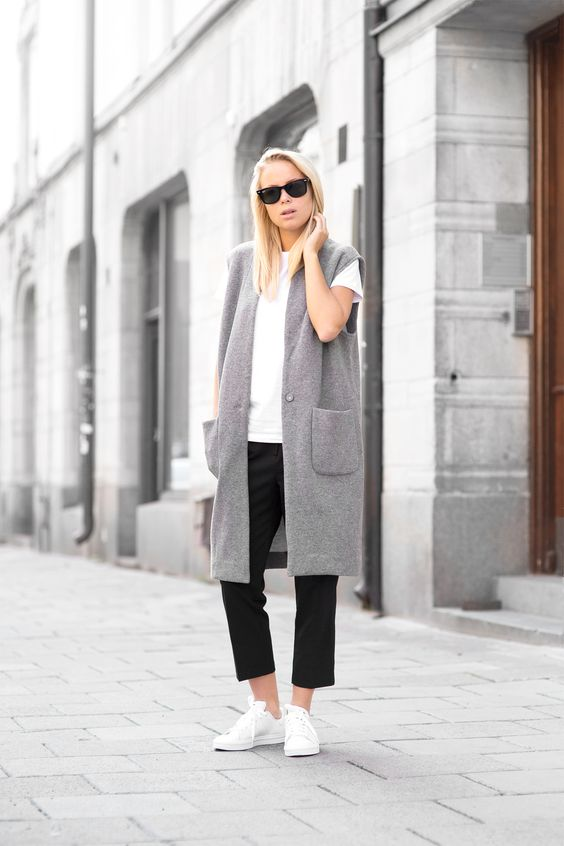 black cropped pants, a white tee, white sneakers and a grey oversized long vest for a trendy feel