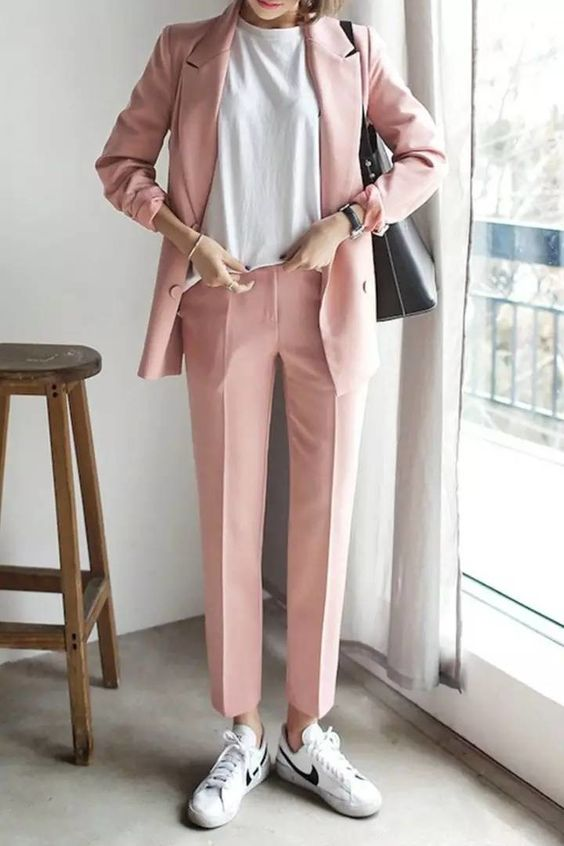 a light pink pantsuit with a white tee and white sneakers plus a black bag looks casual