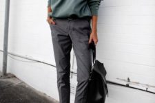 14 an olive green sweatshirt, cropped grey trousers, black slipons and a black backpack