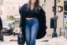 14 blue jeans, a black crop top, a black coat and strappy heels, a black bag