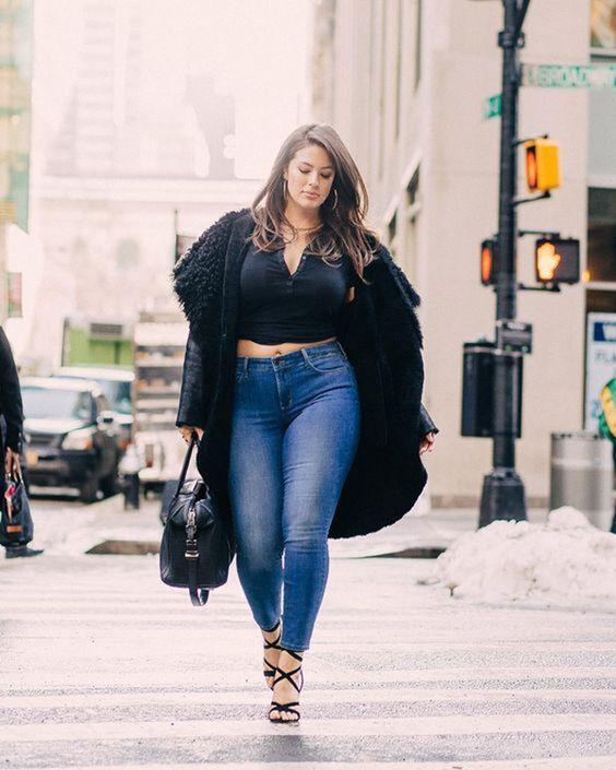blue jeans, a black crop top, a black coat and strappy heels, a black bag